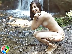 Charming girl with a perfect body poses naked and gets wet in the waterfall on hd movies.